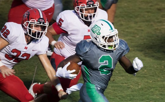 Fort Myers High Schools' Yasias Young, right, breaks free from North Fort Myers defenders on Friday at Edison Stadium in Fort Myers. Fort Myers beat North 48-3.