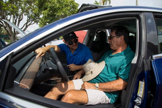 A man test drives a Tesla Model 3 at an electric car show in September.