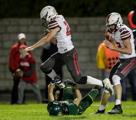 Pulaski's Benjamin Redlin (22) leaps over Green Bay Preble's Ricardo Aguado (2) on a run during their football game Friday, September 13, 2019, at Green Bay Preble High School in Green Bay, Wis.