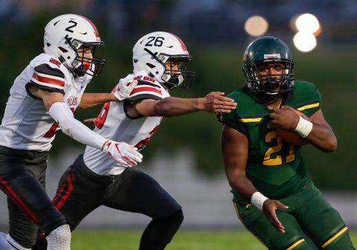 Pulaski's Jake Binkowski (2) and Kyle Ruechel (26) close in on Green Bay Preble's Jamar Howell (21) on a run during their football game Friday, September 13, 2019, at Green Bay Preble High School in Green Bay, Wis.