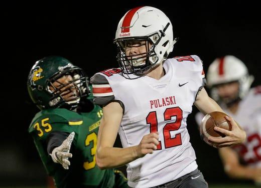 Pulaski's Nash Lemerond (12) outruns Green Bay Preble's Will Gauger (35) during their football game Friday, September 13, 2019, at Green Bay Preble High School in Green Bay, Wis.