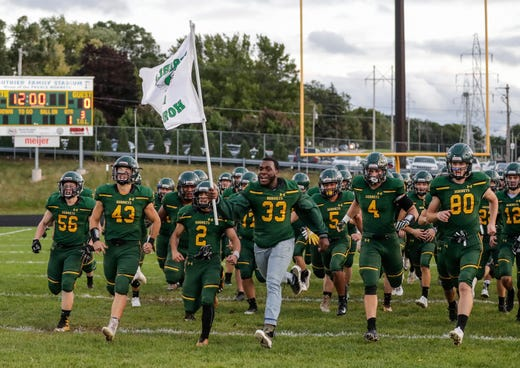 Green Bay Preble is led onto the field by Michael Williams (33) before their game against Pulaski Friday, September 13, 2019, at Green Bay Preble High School in Green Bay, Wis.
