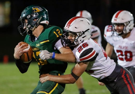 Green Bay Preble's quarterback Ryan Buergi (12) is tackled by Pulaski's Kyle Ruechel (26) on a keeper during their football game Friday, September 13, 2019, at Green Bay Preble High School in Green Bay, Wis.