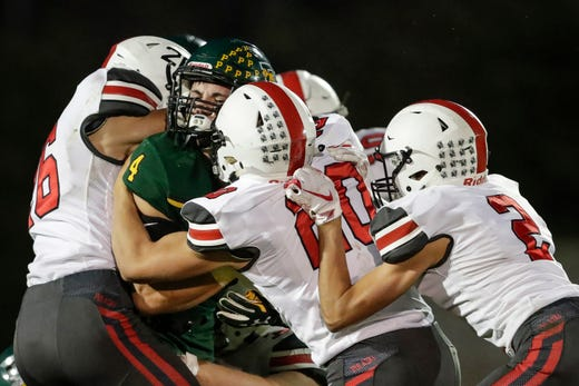 Green Bay Preble's Gatlin Wanner (4) is swarmed by Pulaski defenders on a running play during their football game Friday, September 13, 2019, at Green Bay Preble High School in Green Bay, Wis.