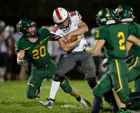 Pulaski's Benjamin Redlin (22) braces for a hit from Green Bay Preble's Connor Shefchik (20) during their football game Friday, September 13, 2019, at Green Bay Preble High School in Green Bay, Wis.