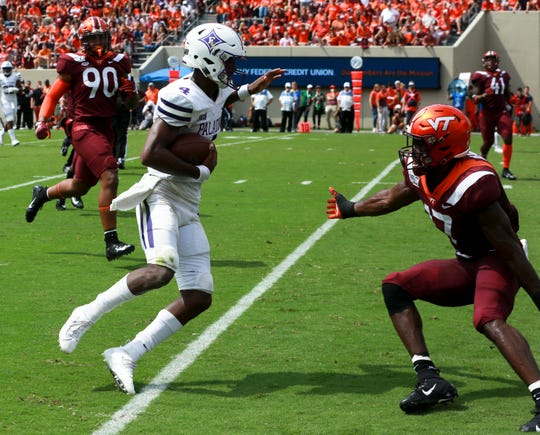 Furman quarterback Darren Grainger (4) eludes Virginia Tech defender Divine Deablo (17) for a 15-yard touchdown during the first half Saturday in Blacksburg, Va.
