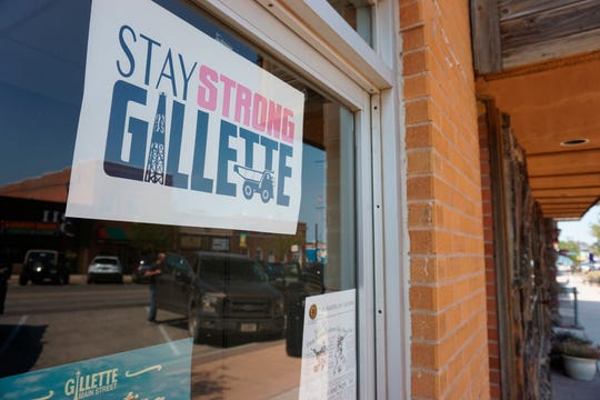 A poster on a a Gillette, Wyo., storefront urges locals to stay strong amid hardship in the Eagle Butte mine just north of Gillette.