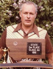 Former C.M. Russell head boys' track coach Ron Frost holding the runner-up trophy from the 1981 Class AA State track meet. Frost died Wednesday at age 79.