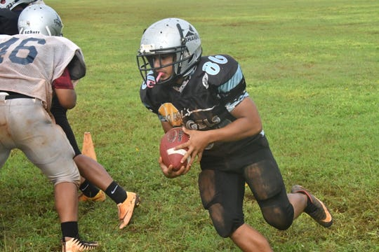 Freshman Jon Sablan runs the ball during drills at practice Sept. 11 at Simon Sanchez High School.