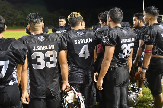 Sablan brothers No. 33 Jon, No. 4 Jeremiah and No. 35 Josh on the sidelines during the Simon Sanchez game against Tiyan Sept. 7 at Okkodo field.