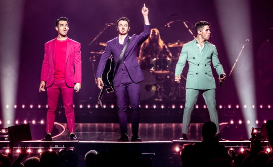 The Jonas Brothers, from left, Joe, Kevin, and Nick, perform Friday at Bankers Life Fieldhouse.