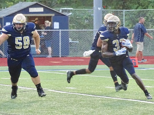 Lancaster running back George Sherrick looks for running room as Noah Burnside leads the way in the Golden Gales' 21-7 loss to Hilliard Darby.