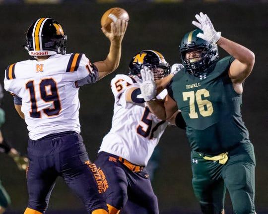 Howell lineman Grant Porter pressures Northville quarterback Tyler Peterson during the Highlanders' 27-14 victory on Friday, Sept. 13, 2019.