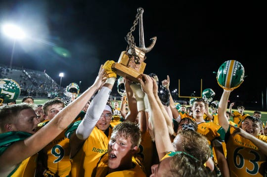 The Highlanders hoist the Anchor trophy after they beat rival New Albany 50-14 Friday, Sept. 13, 2019 in Floyds Knobs, Ind.