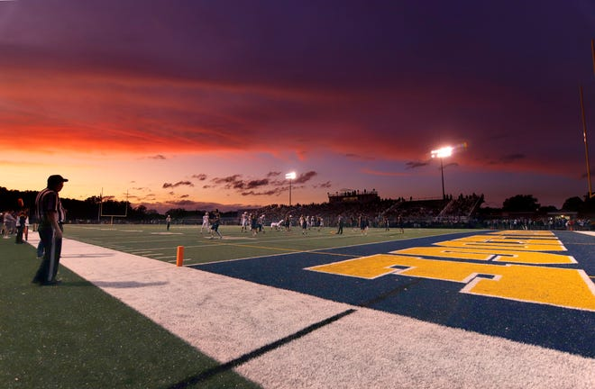 East Lansing and Grand Ledge play as the sun sets, Friday, Sept. 13, 2019, in Grand Ledge, Mich. East Lansing won 42-3.