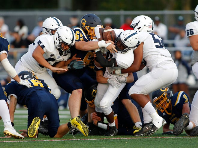 East Lansing's Asher Gregory is gang tackled by Grand Ledge, Friday, Sept. 13, 2019, in Grand Ledge, Mich. East Lansing won 42-3.