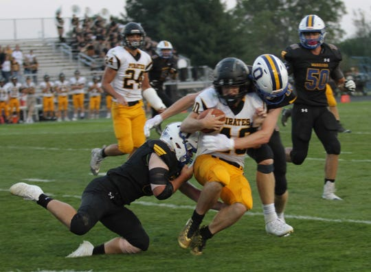 Two Ontario defenders bring down a Black River ballcarrier Friday night in a game that was completed on Saturday morning.