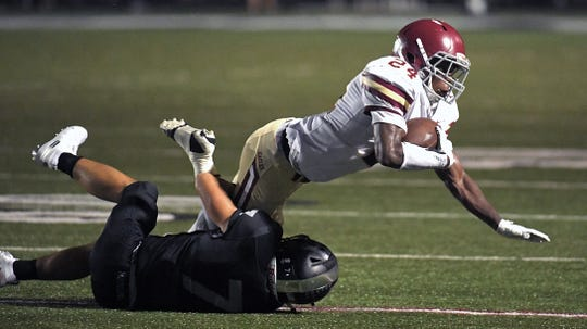 Evangelical Christian School running back  Jaylen Greenwood (24) is tackled by Houston High's Will Stegall (7) during a game in Germantown, Tenn. on Friday, Sept. 13, 2019.