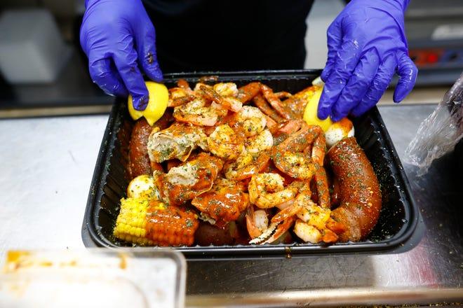 DeSha Pullen prepares a cajun butter topped seafood platter at Krab Kingz in Bartlett on Thursday, Sept. 12, 2019.