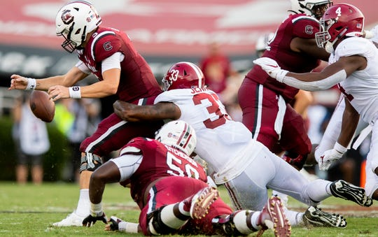 South Carolina quarterback Ryan Hilinski (3) fumbles as hi is hit by Alabama linebacker Anfernee Jennings (33) at Williams-Brice Stadium in Columbia, S.C., on Saturday September 14, 2019.