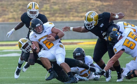 Kennesaw quarterback Daniel David (2) falls backwards as he's pulled down for a tackle.