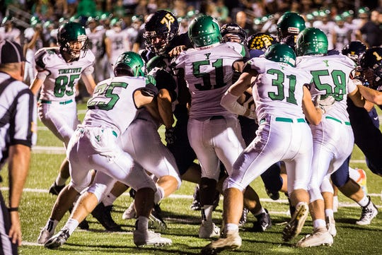 FILE -- Yorktown's defense tries to fend off Delta during their game at Delta High School Friday, Sept. 13, 2019.