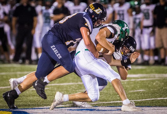 A pair of Delta defenders takes down Reid Neal for a sack during the game against Yorktown at Delta High School Friday, Sept. 13, 2019.