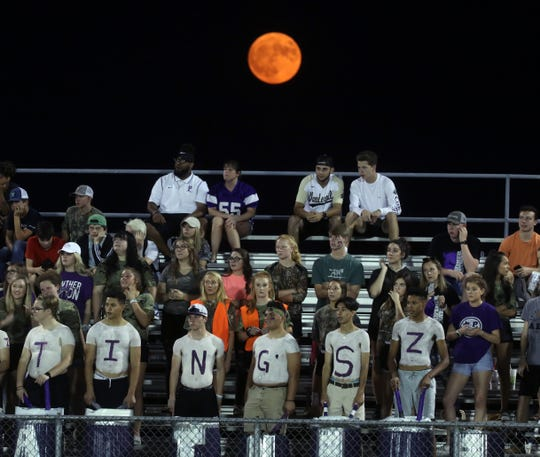 The Harvest Moon rises above Portland fans sitting in the stands at Greenbrier High School Friday, Sep. 13, 2019.