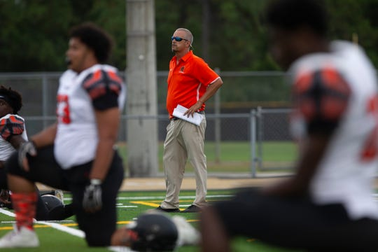 Lely High School football coach JJ Everage watches his team before their game against Golden Gate, Friday, Sept. 13, 2019, at Titan Stadium.