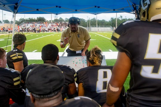 Golden Gate High School Coach Nick Bigica talks with his offense during their game against Lely, Friday, Sept. 13, 2019, at Titan Stadium.