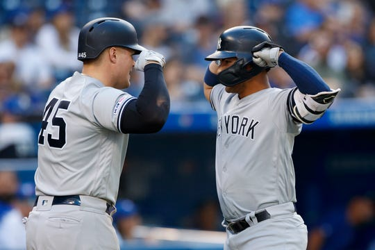 Luke Voit #45 of the New York Yankees and Gleyber Torres #25 celebrate Torres' two-run home run in the sixth inning of their MLB game against the Toronto Blue Jays at Rogers Centre on September 14, 2019 in Toronto, Canada.