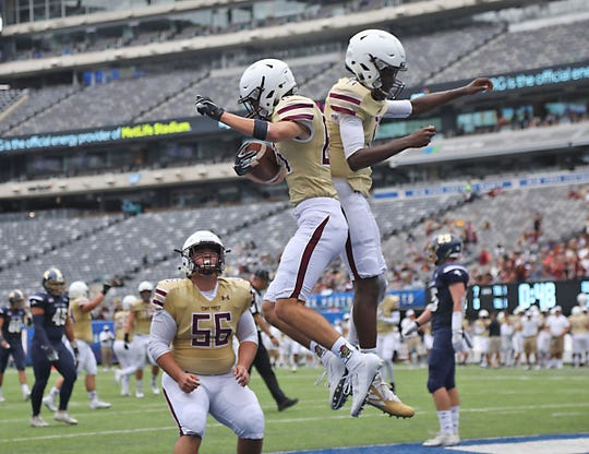 William Stone and Darius Wilson of Iona Prep celebrate a TD by Stone during the Battle for the Bridge High School Football competition at Metlife Stadium in East Rutherford , NJ on September 14, 2019.