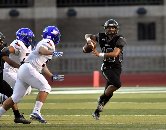 Oñate QB Matthew Saenz rolls to his left looking for an open receiver versus Americas High School on Friday night at Field of Dreams.