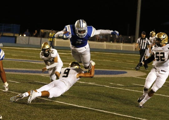 Carlsbad's Shamar Smith tries to jump over Coronado's Adrian Martinez during Carlsbad's homecoming game on Sept. 13, 2019. Smith scored two touchdowns in the game and Carlsbad won, 33-20.