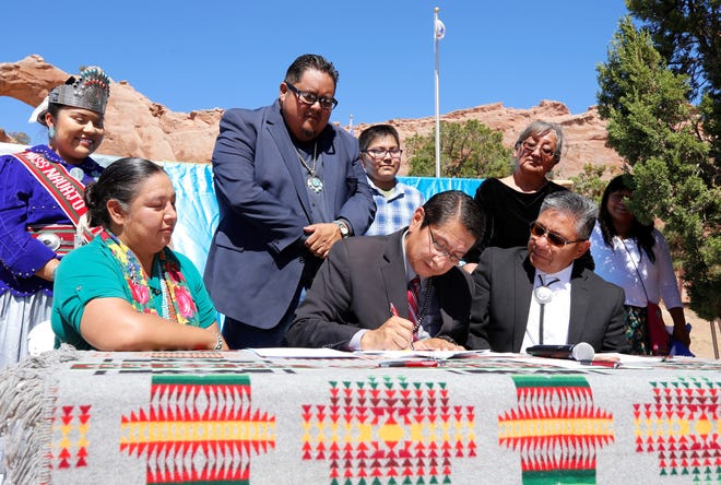 Navajo Nation President Jonathan Nez, lower center, signs the comprehensive budget for fiscal year 2020 on Sept. 13, 2019 in Window Rock, Arizona.