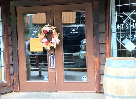 A wreath and a note of the front door of The Hunt and Harvest in midtown. The restaurant will be closed to pay respect for those affected by the tragedy.
