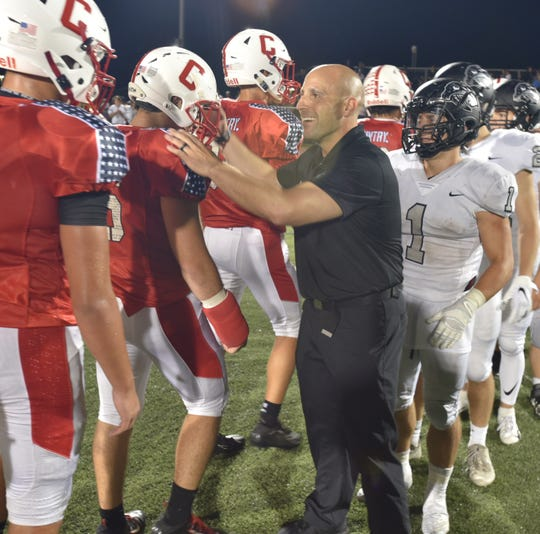 A Plymouth assistant coach congratulates Canton Chief players after his Plymouth Wildcats beat them in a well-played game on Sept. 13, 2019, 15-13.