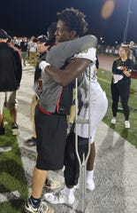 Plymouth Wildcat Ivan Davis, who injured his knee late in the game, gets a congratulatory and heal-up-quick hug from a Canton coach.