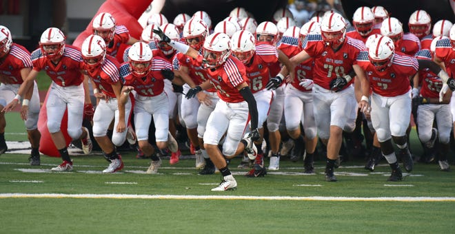 The Canton Chiefs are led out of their tunneyl by Atlee Mark, center, in their Sept. 13, 2019 game against Plymouth High.