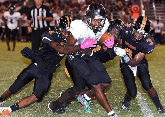 A Northwest High player is surrounded by Opelousas High defensive back Collin Guillory and a teammate Friday night during the Zydeco Classic football game at Donald Gardner Stadium. The Raiders won the contest 48-20.