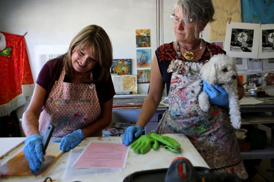 Tracey Genkins, left, of Yucca Valley works on an encaustic painting as artist Gretchen Grunt helps her at Grunt's artist compound during The Joshua Tree National Park Art Exposition in Twentynine Palms, Calif., on Saturday, September 14, 2019.