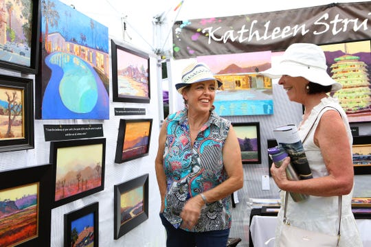 Artist Kathleen Strukoff, left, of San Juan Capistrano shows Mickie Hezlep of Newport Beach her work during The Joshua Tree National Park Art Exposition in Twentynine Palms, Calif., on Saturday, September 14, 2019.