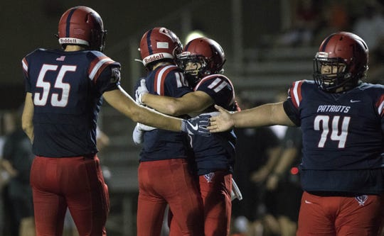 Between American Leadership Academy lineman Micah Ferrin (55) and Helijah Hilai (74) quarterback Rand Jensen (5) and Carter Taylor (11) celebrate their touchdown against  Phoenix Christian the first half of their game in Queen Creek.