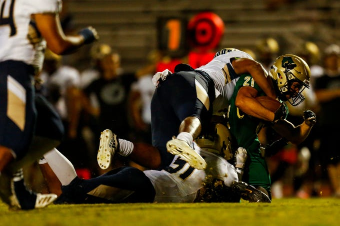 Basha's Andrew Fernandez (21) is tackled in the second half at Basha High School's homecoming game against La Joya Community Friday, September 13, 2019 at in Chandler.