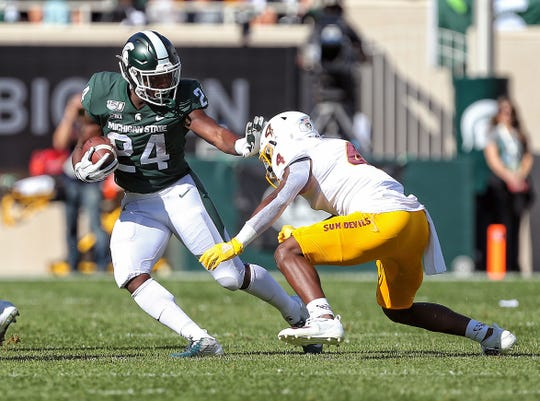 Evan Fields tries to tackle Michigan State running back Elijah Collins during the first quarter of a game Sept. 14 at Spartan Stadium.