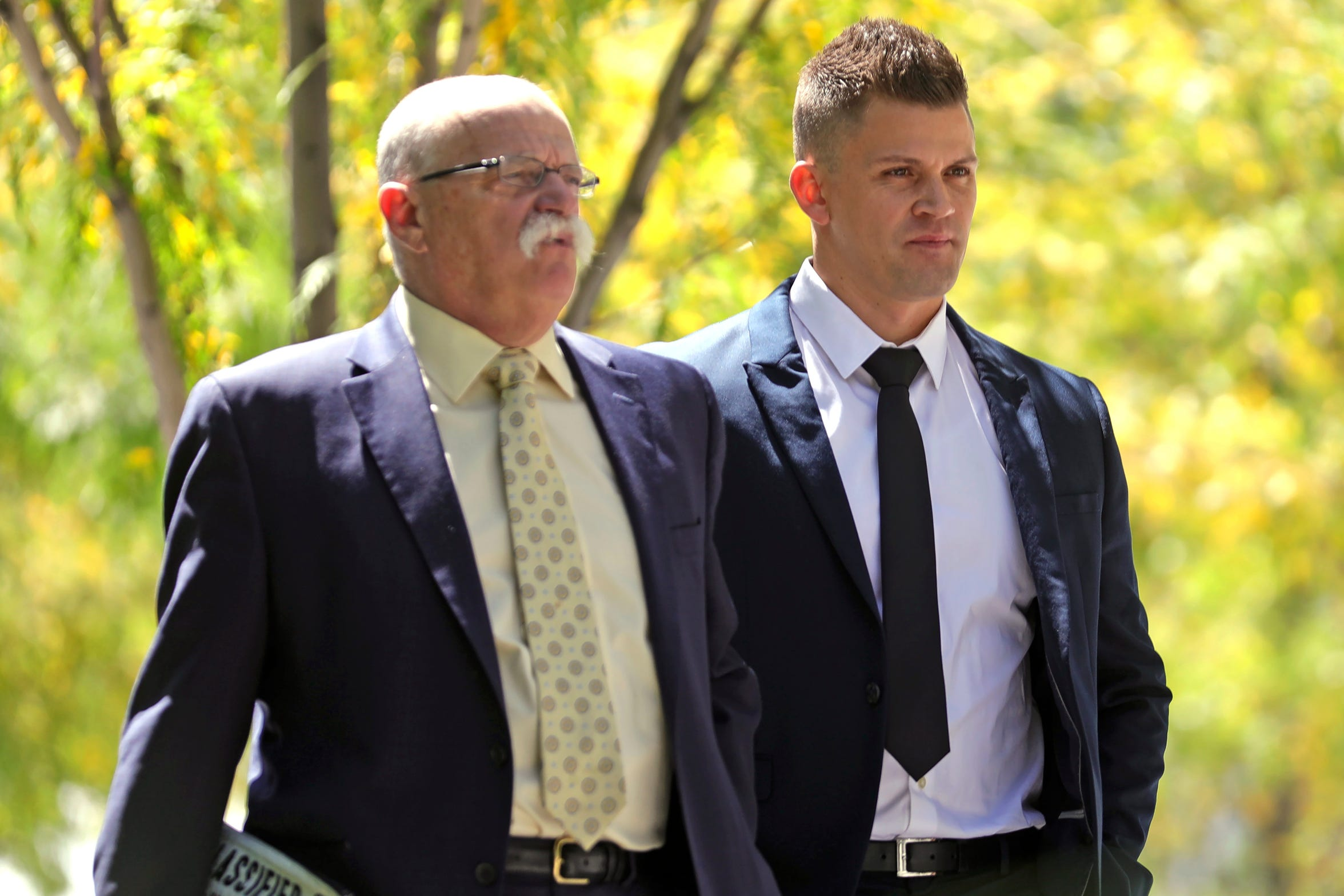 In this Aug. 23, 2019, photo, Jonathan Luke Paz, right, leaves the federal courthouse after testifying, in Salt Lake City. He has pleaded guilty to helping Aaron Shamo press potentially poisonous fentanyl-laced counterfeit prescription drug pills and agreed to testify against him.