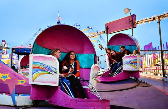 From left, Jennifer Petenbrink and Karina Ortiz, both of Hanover, and Riley Clark, 11, Brianna Carey, Alex Gamber, and Leah Clark, 9, all of Cumberland County, ride the Tilt-A-Whirl at York Fair in West Manchester Township, Friday, Sept. 13, 2019. Dawn J. Sagert photo