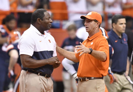 Syracuse Orange head coach Dino Babers (left) and Clemson Tigers head coach Dabo Swinney meet prior to a game at the Carrier Dome.