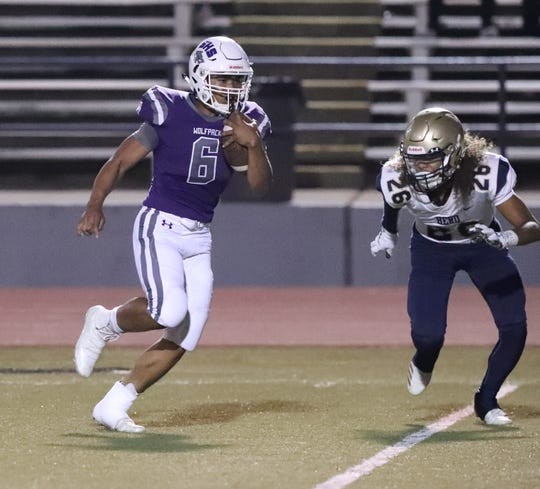 Shasta High's Johari Woods, left, carries the ball Friday, Sept. 13, 2019. Shasta lost to Elk Grove 50-14.