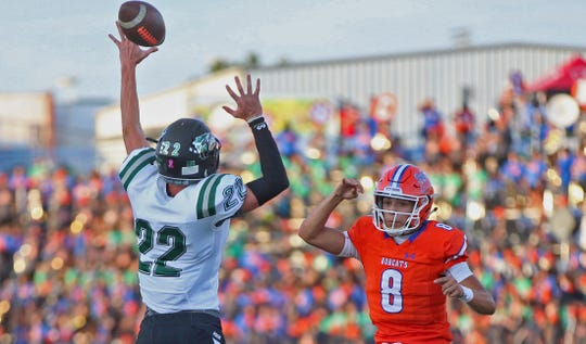 Malachi Brown, right, tosses a pass over an opponent for the Bobcats against Cedar Park on Friday, September 13, 2019.